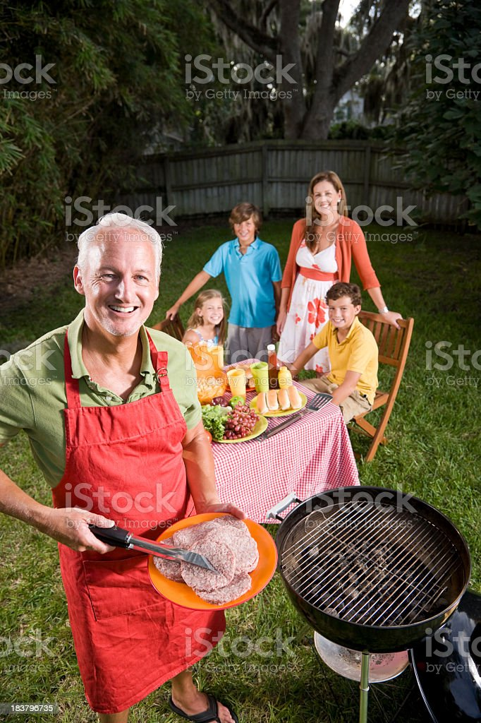 Family grilling burgers in back yard royalty-free stock photo