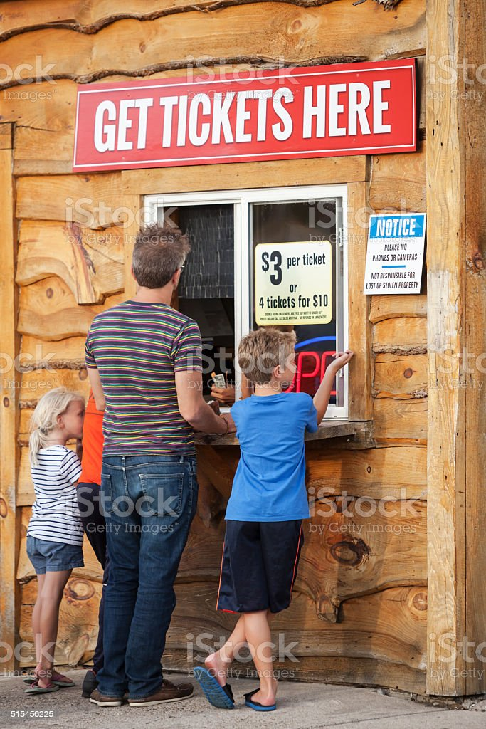 Family Group Purchasing Tickets at a Ticket Booth stock photo