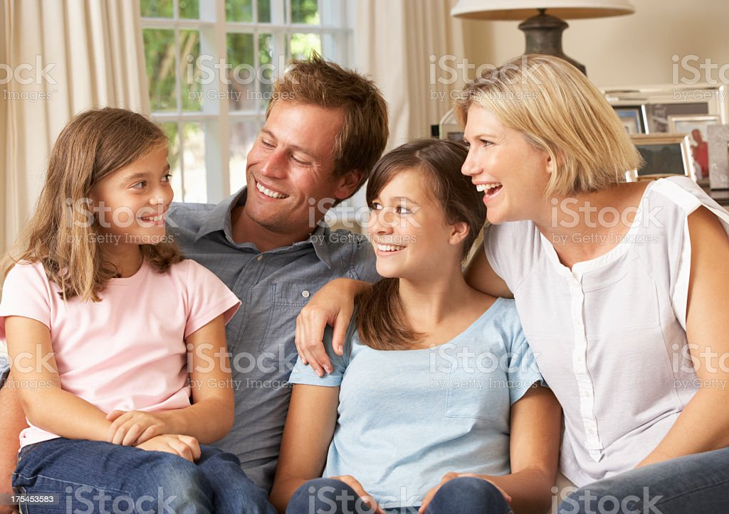 Family Group Sitting On Sofa Indoors royalty-free stock photo