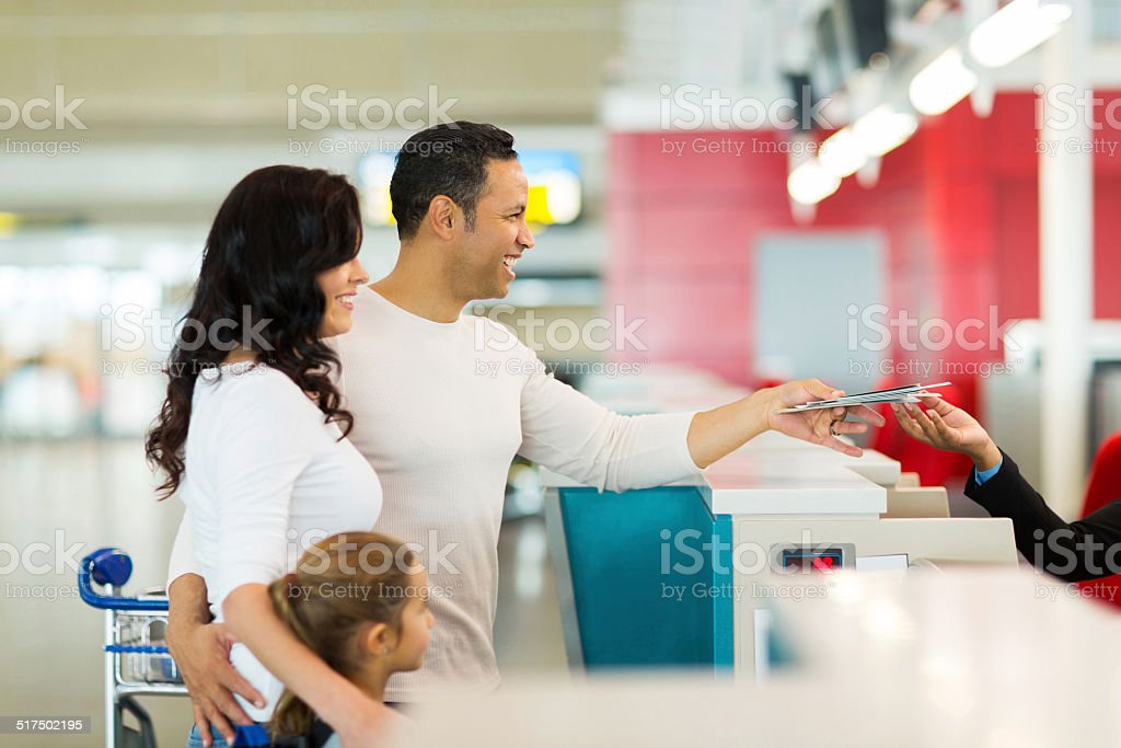family handing over air ticket at airport at check in counter stock photo