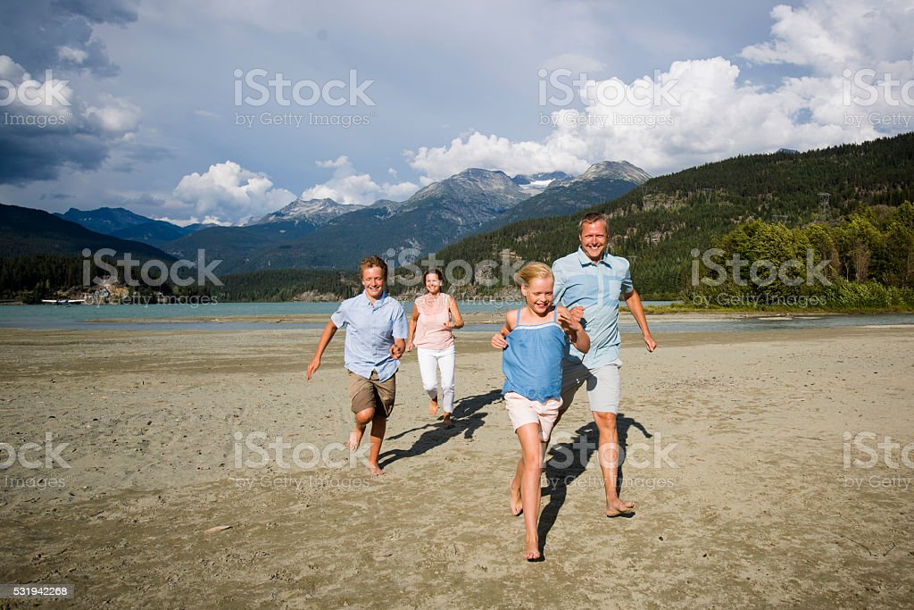 Family hanging out  and chasing each other on beach. stock photo