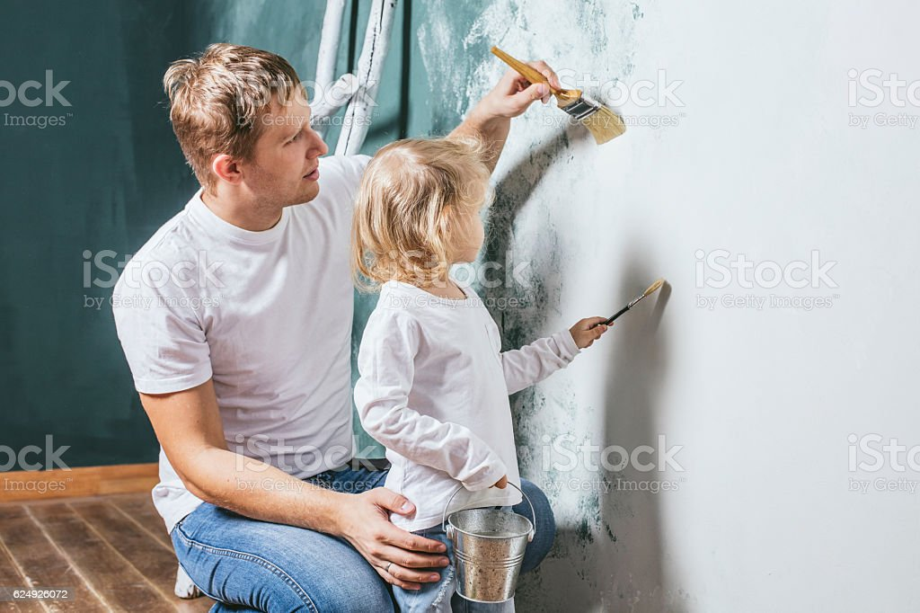 Family, happy daughter with dad doing home repair, paint walls, stock photo