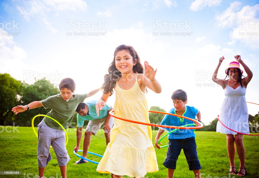 A family has fun hula hooping on a summer day at the park stock photo
