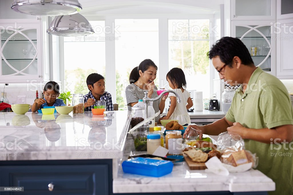Family Having Breakfast And Making Lunches In Kitchen stock photo