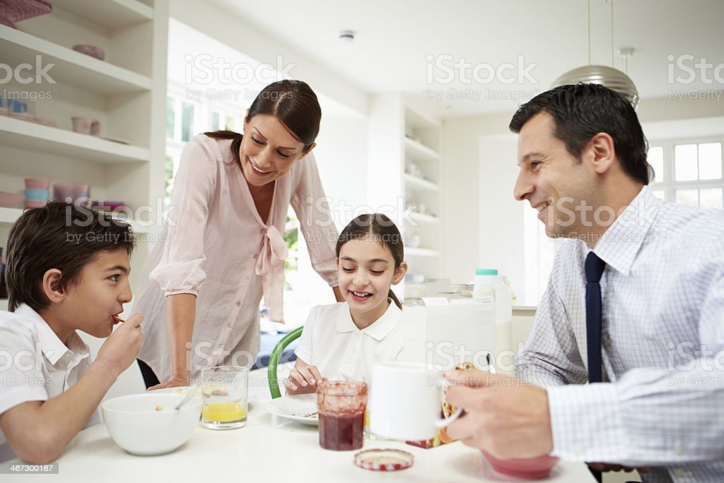 Family Having Breakfast Before Husband Goes To Work stock photo