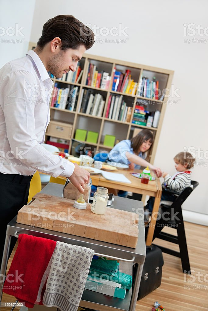 Family having Breakfast - Father preparing a Bottle royalty-free stock photo