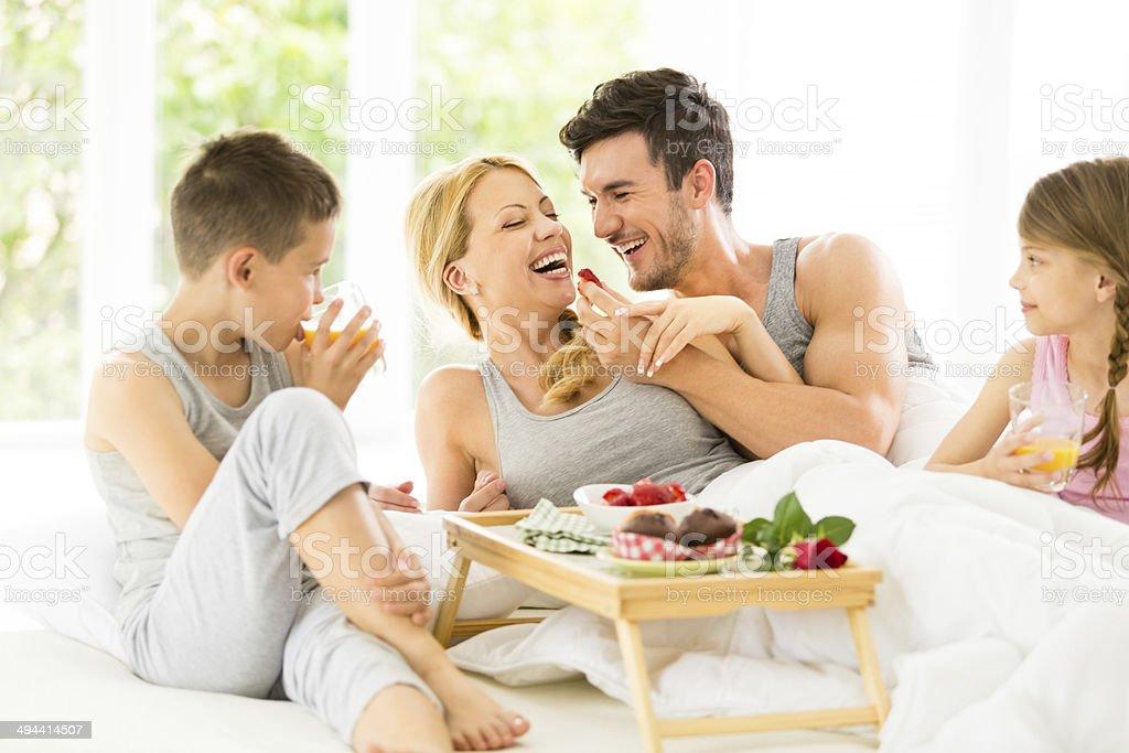 Family having breakfast in bed stock photo