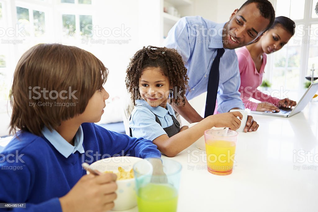 Family Having Breakfast In Kitchen Before School And Work stock photo