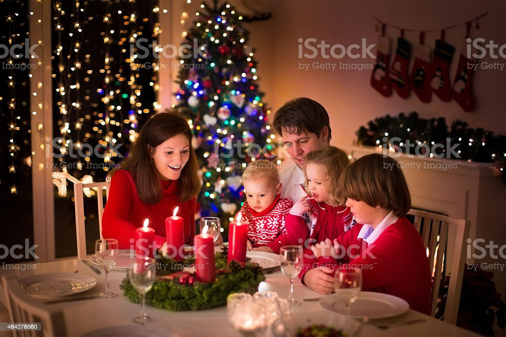 Family having Christmas dinner at fire place stock photo