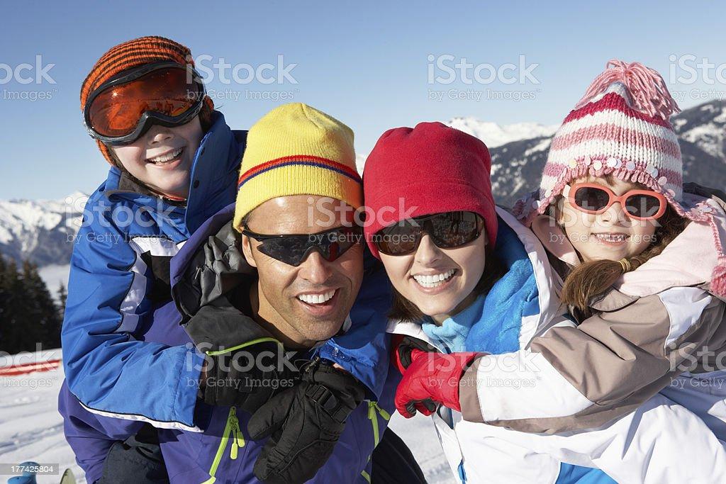 Family Having Fun On Ski Holiday In Mountains stock photo