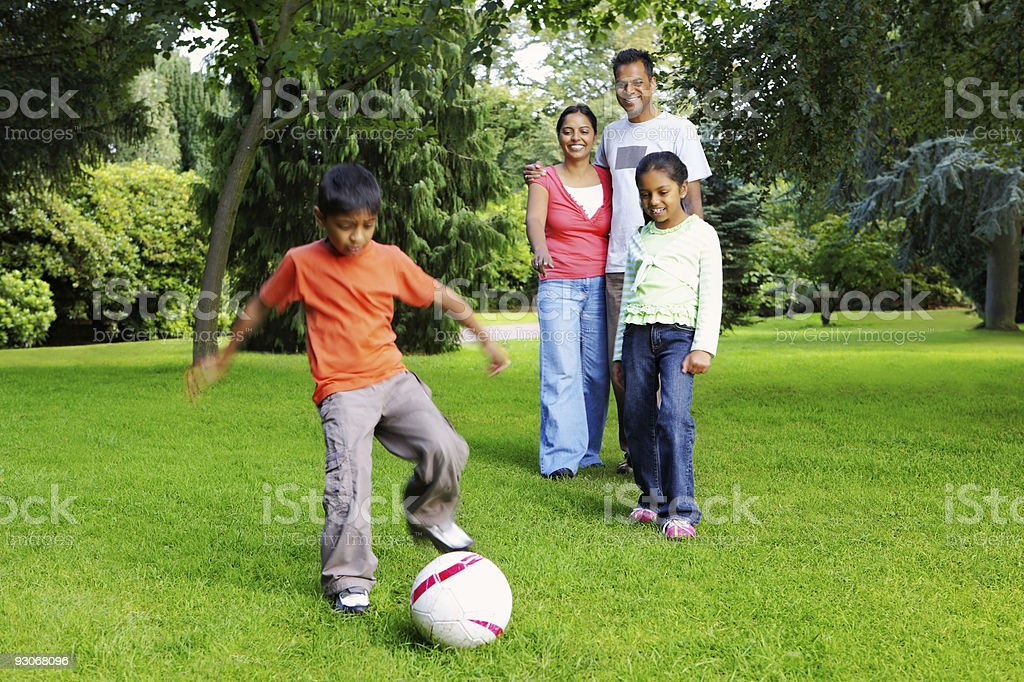 Family having fun playing football in a park royalty-free stock photo