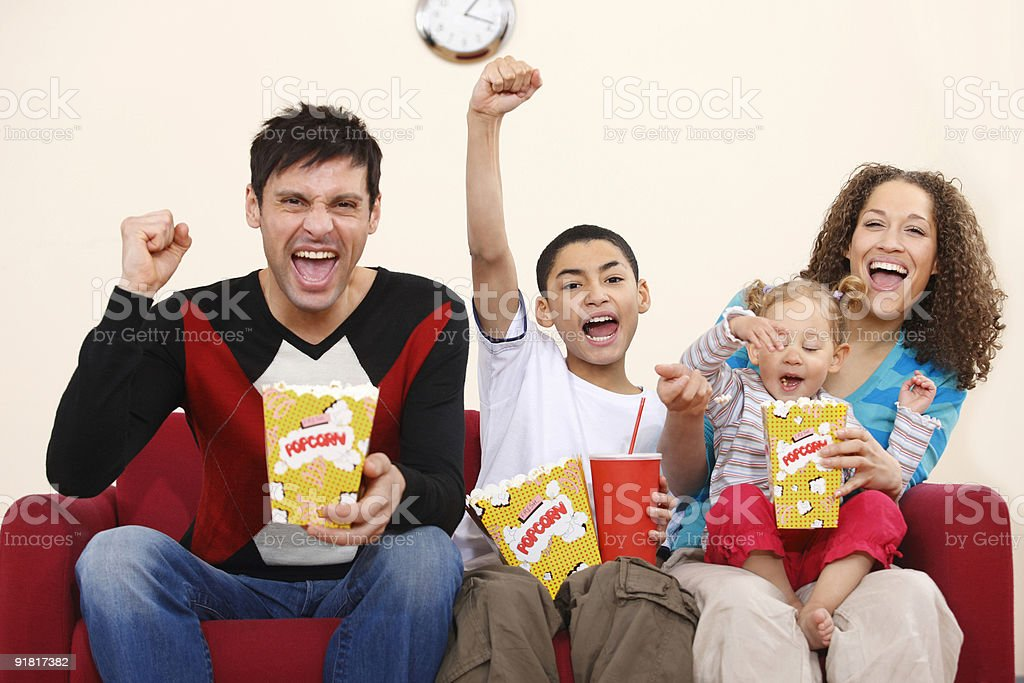 Family having fun watching a movie at home royalty-free stock photo
