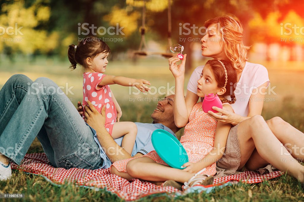 Family Having Fun With Bubbles. stock photo