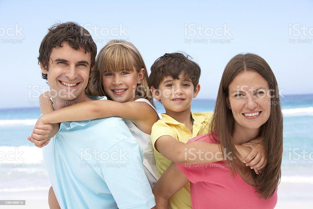 Family Having Piggyback Fun On Beach Holiday stock photo