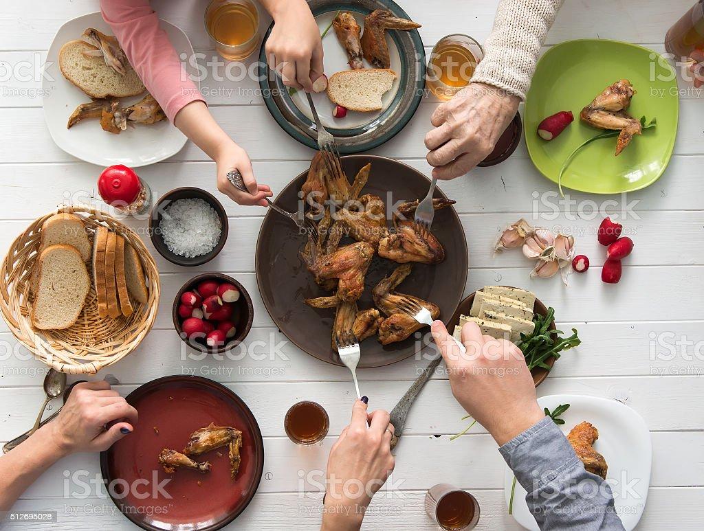 family having roasted chicken wings for dinner stock photo