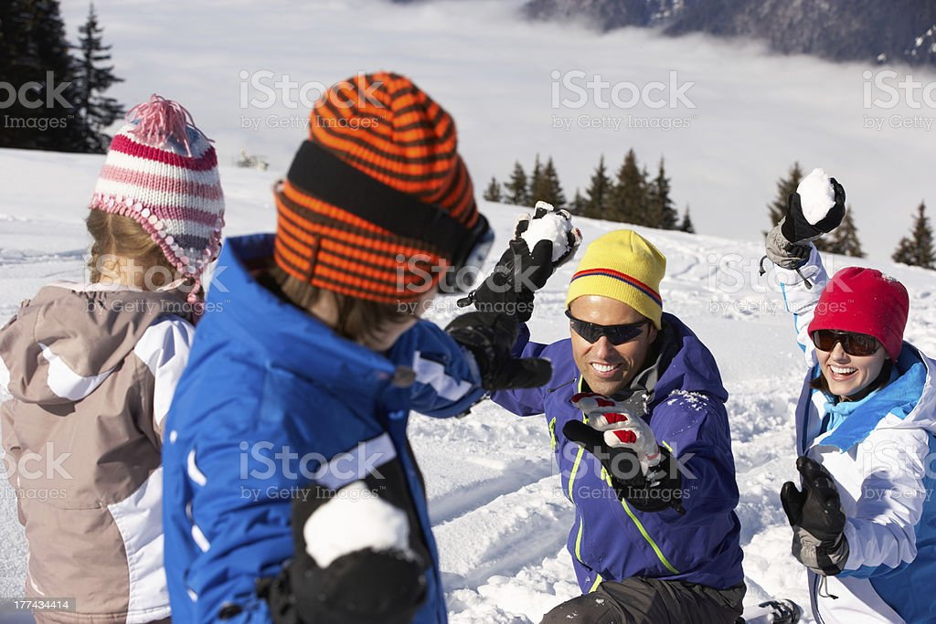 Family Having Snowball Fight On Ski Holiday In Mountains royalty-free stock photo