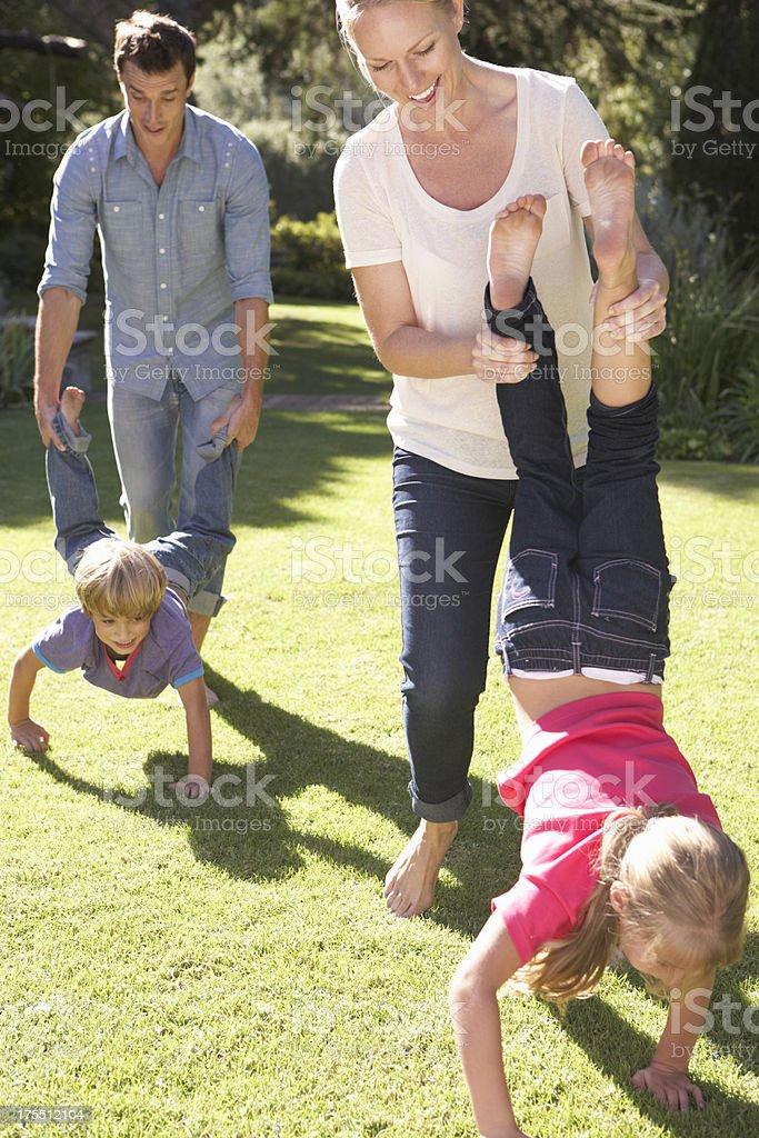 Family Having Wheelbarrow Race In Garden stock photo