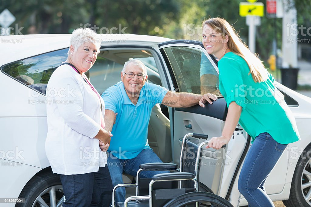 Family helping senior man from car to wheelchair stock photo
