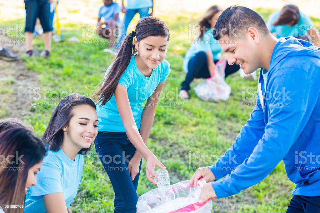 Family helps neighbors clean up park stock photo