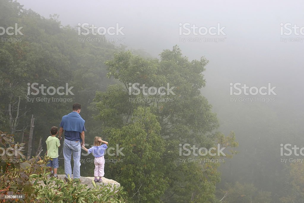 Family hike - Father with two children standing on rock royalty-free stock photo