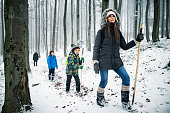 Family hiking in beautiful winter forest