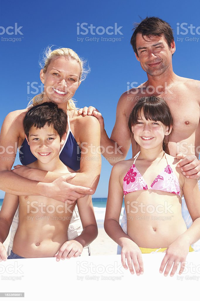 Family holding a sign while enjoying their holiday royalty-free stock photo