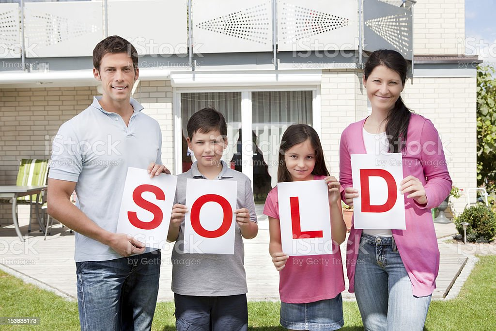 Family holding a sold sign outside their home royalty-free stock photo