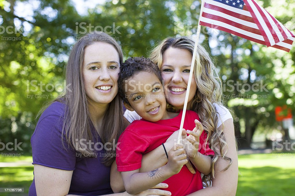 Family holding American flag in a park during summer royalty-free stock photo