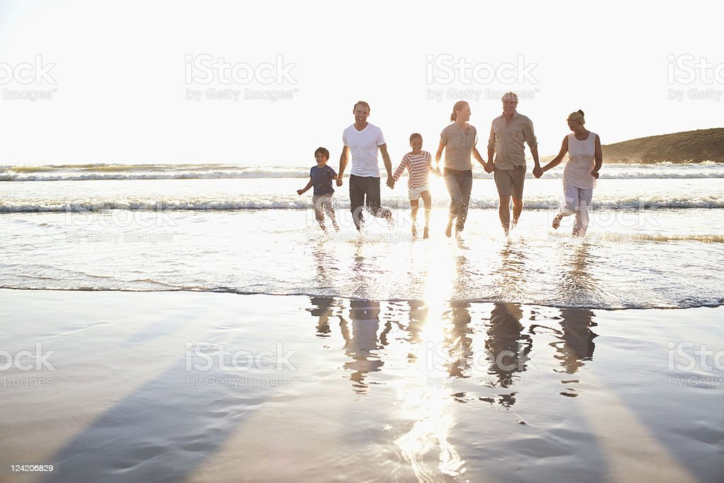 Family holding hands in water at beach stock photo