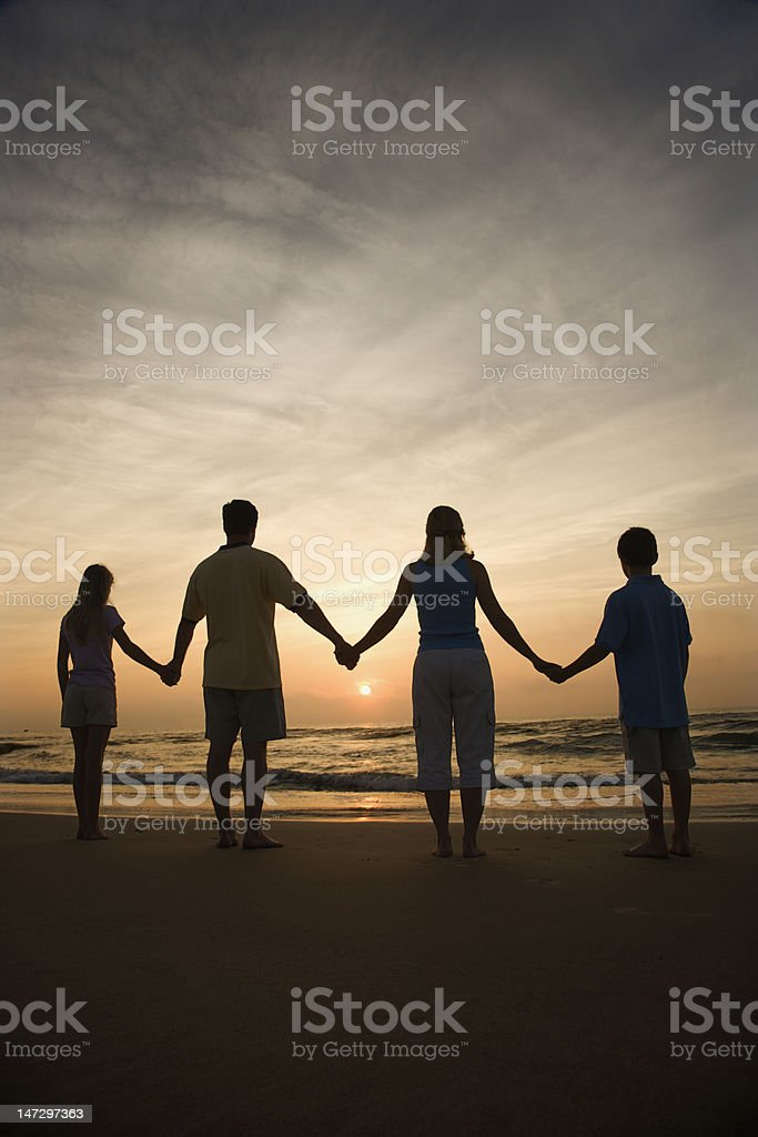 A family holding hands on a beach during sunset royalty-free stock photo