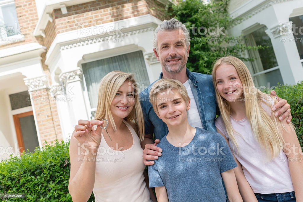 Family holding keys to their new house stock photo