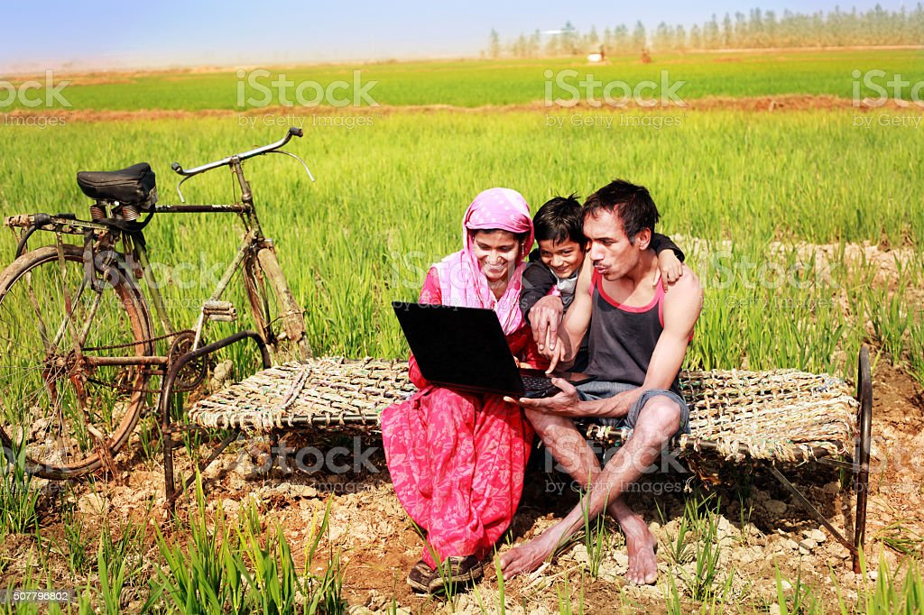 Family Holding Laptop in the wheat field stock photo