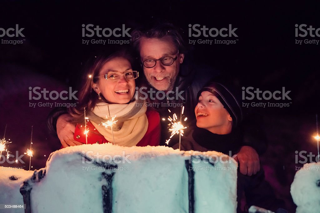 Family holding sparkling Bengal fire outdoors at night in winter. stock photo