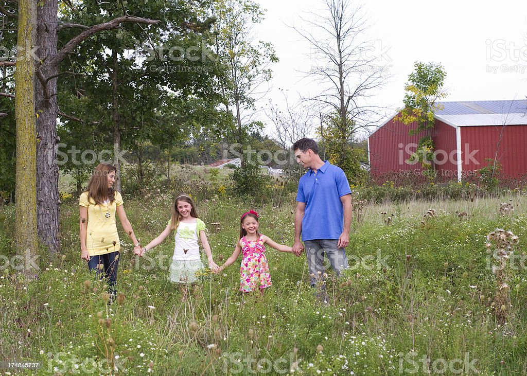 family holds hands in a field with red barn royalty-free stock photo