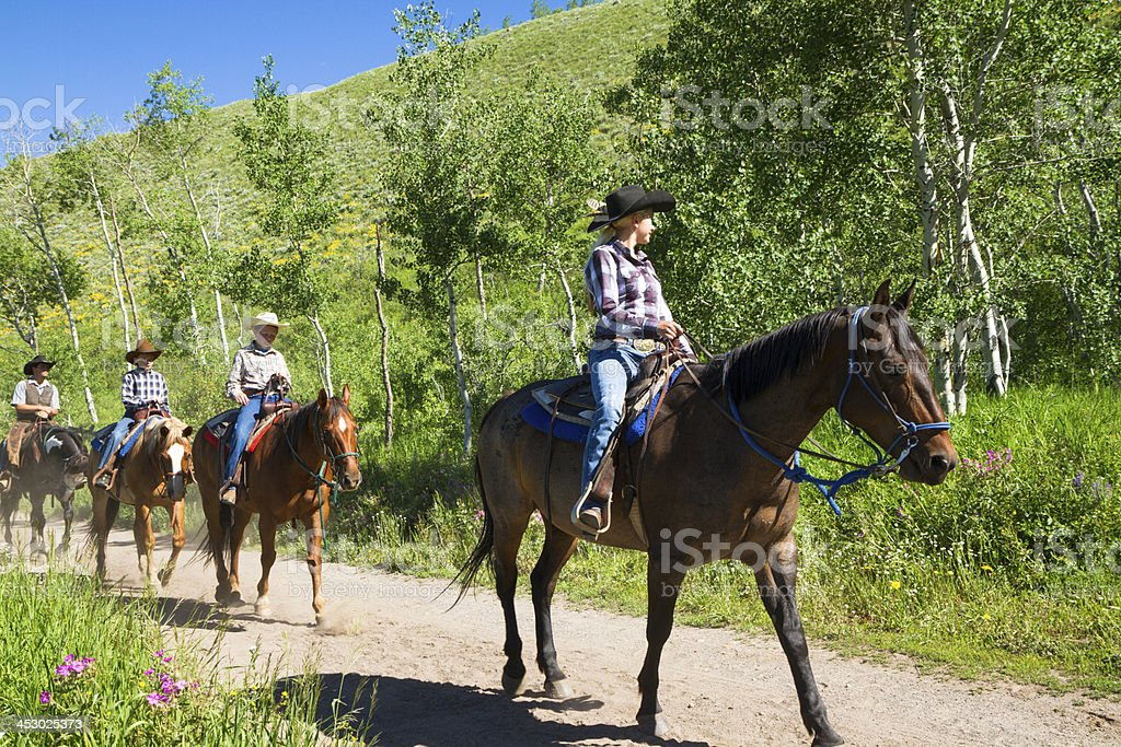 Family Horseback Riding On A Trail stock photo
