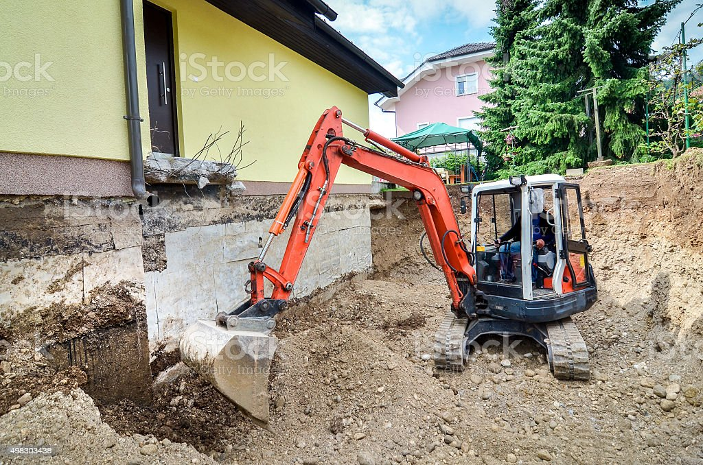 Family house is being rebuilt with the help of excavator stock photo