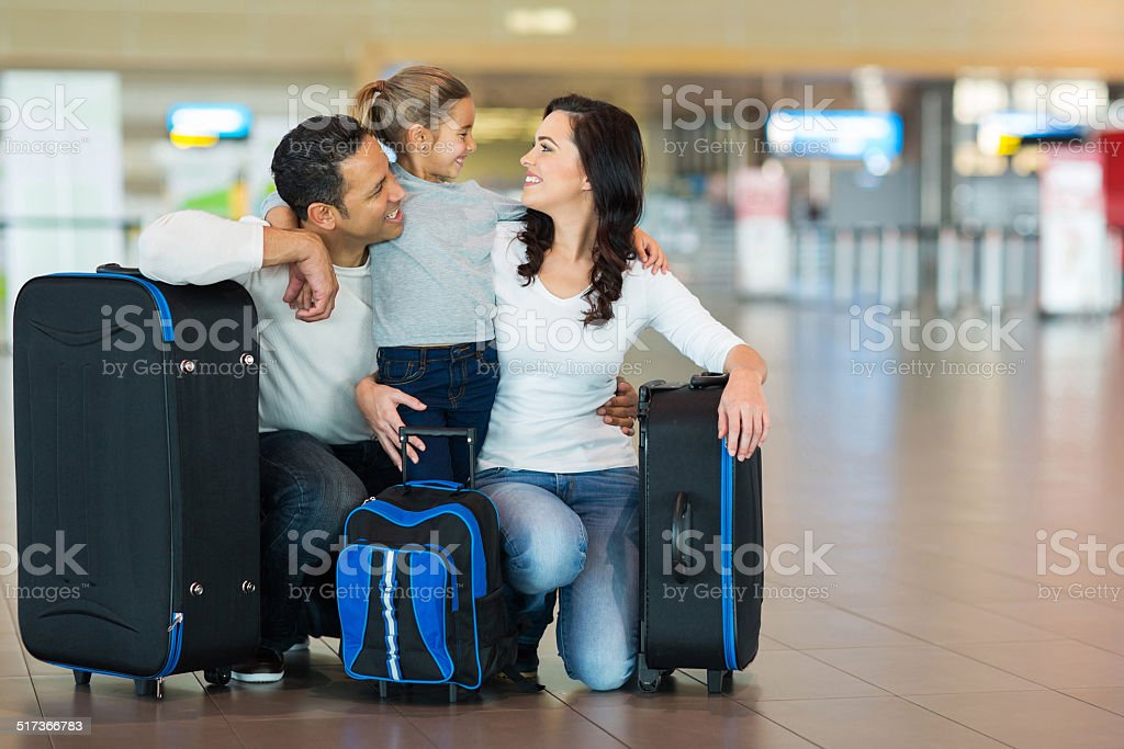 family hugging at airport stock photo