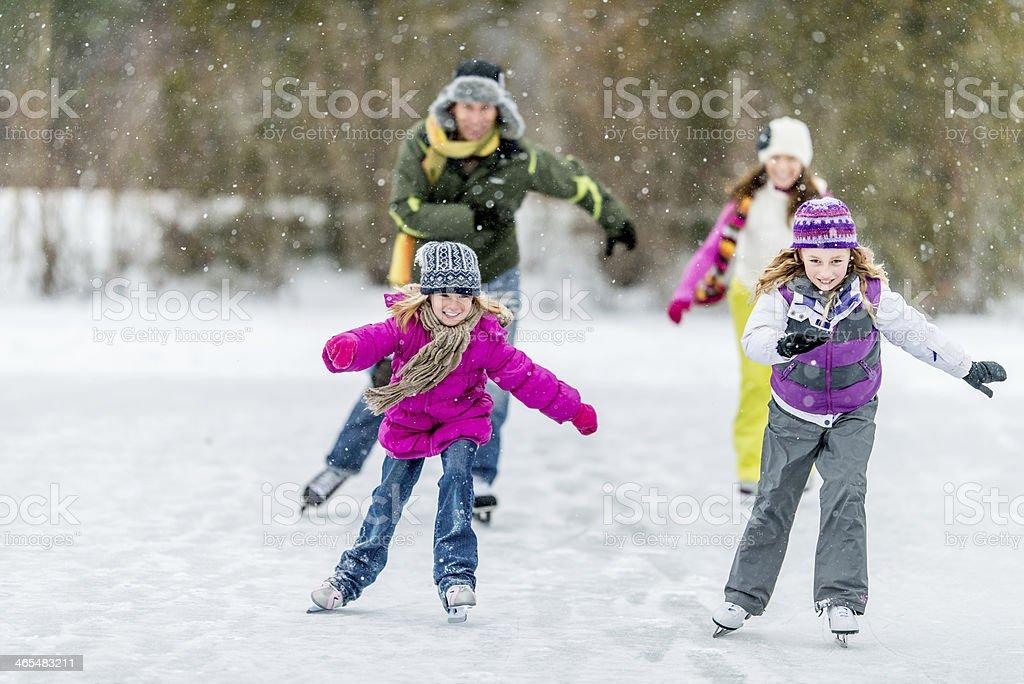 Family Ice-Skating on Pond stock photo
