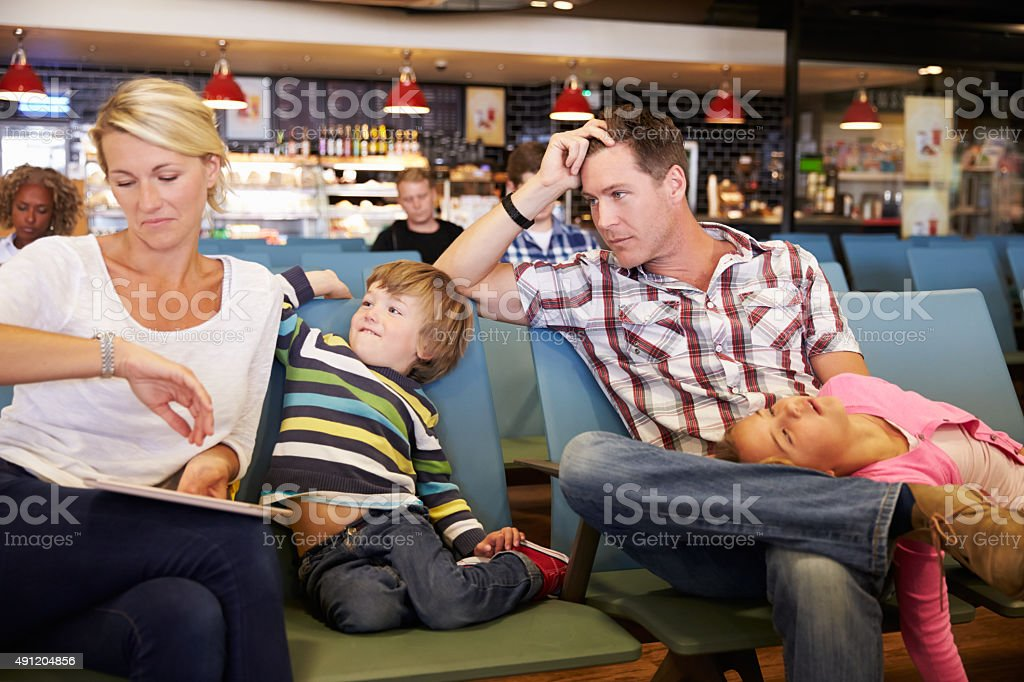 Family In Airport Departure Lounge Wait For Delayed Flight stock photo