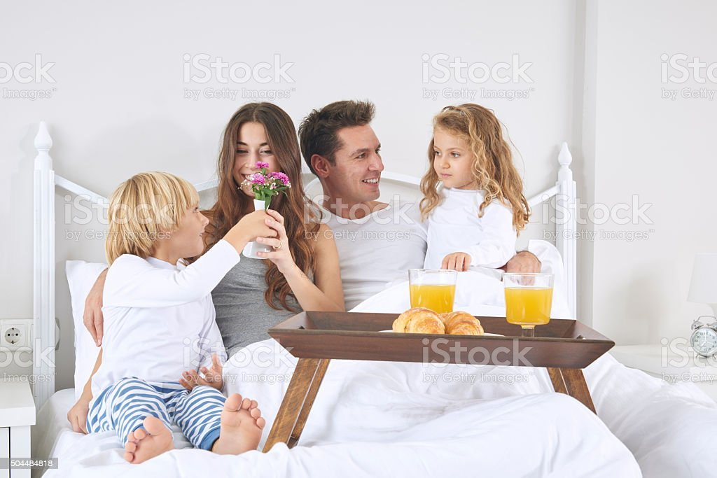 Family in bed and making breakfast stock photo