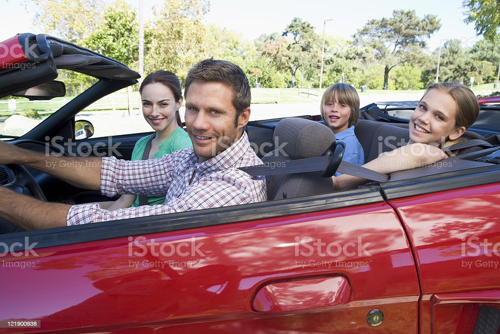 Family in convertible car smiling royalty-free stock photo