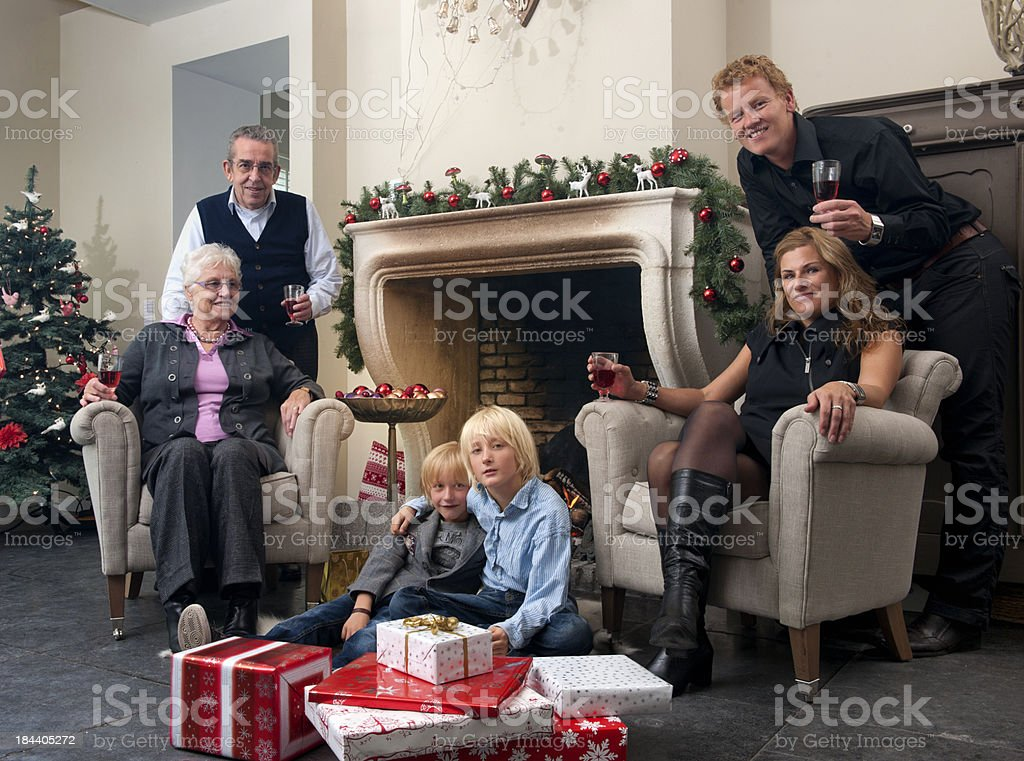 family in front of fireplace celebrating Christmas royalty-free stock photo