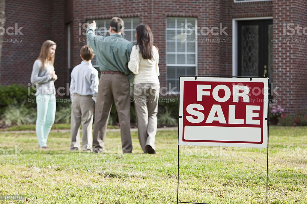 Family in front of home for sale stock photo