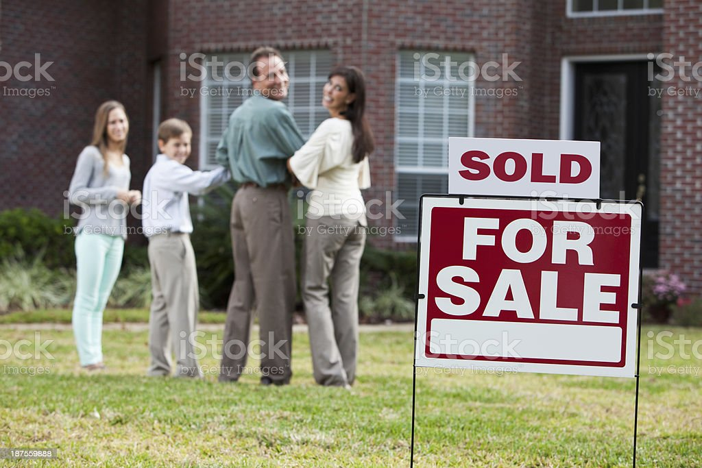Family in front of home with SOLD sign stock photo