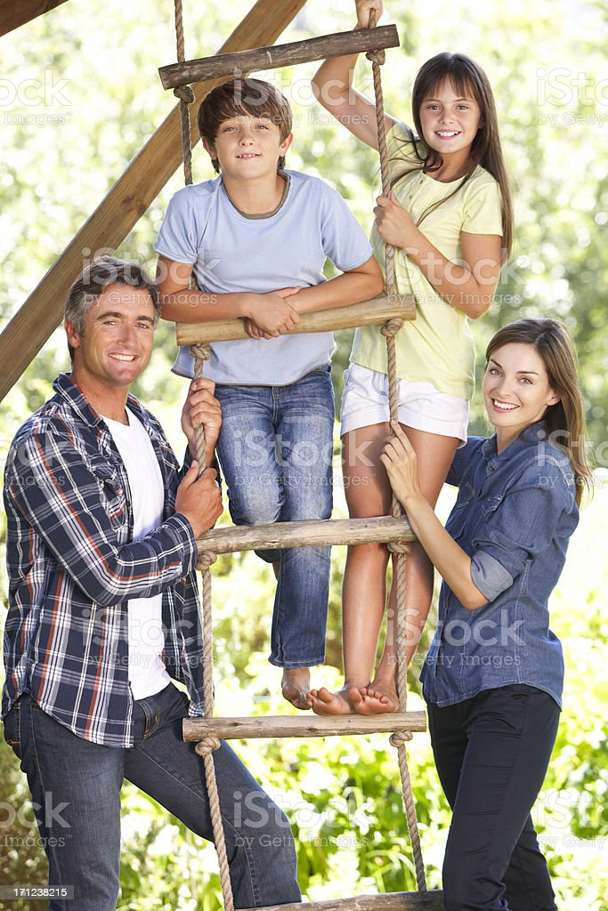 Family In Garden By Treehouse stock photo