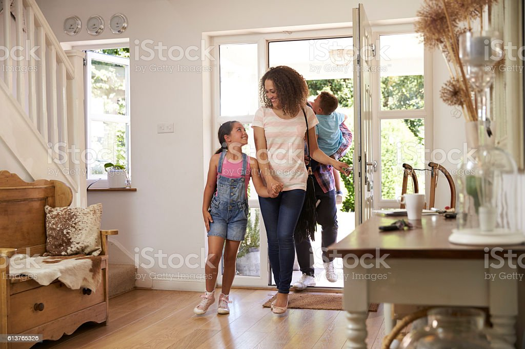 Family In Hallway Returning Home Together stock photo