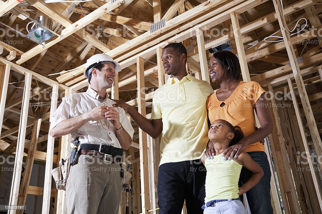 Family in house under construction with builder royalty-free stock photo