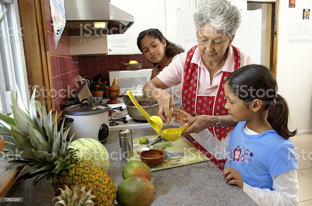 Family in kitchen, grandmother helping youngest granddaughter (6-12) stock photo