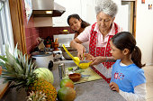 Family in kitchen, grandmother helping youngest granddaughter (6-12)