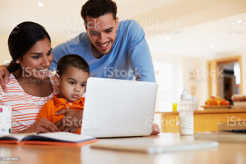 Family In Kitchen Looking At Laptop Together stock photo